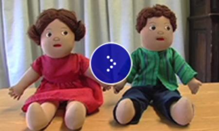 Picture of two dolls, on the left is a female doll dressed in red, and on the right is the male doll dressed in green.