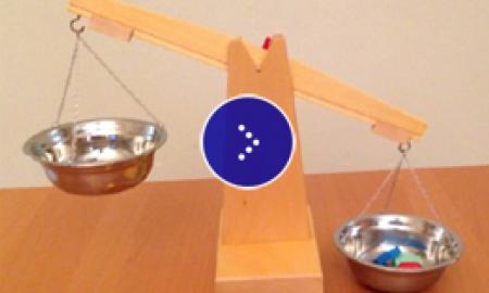 A wooden scale with a silver bowl of objects that weighed down the other empty bowl.