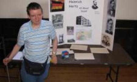 boy stands in front of his science project