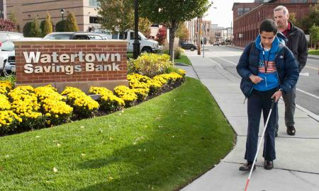 A teenager travels with his cane outside a bank.