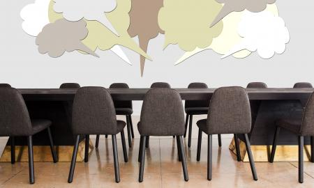 A table with chairs around and thought bubbles above it