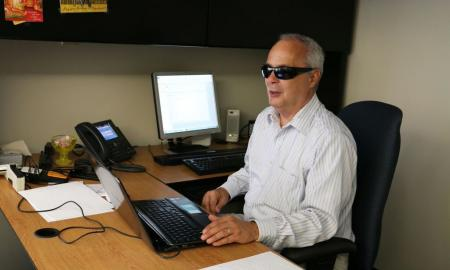 Man who is blind sitting at office desk
