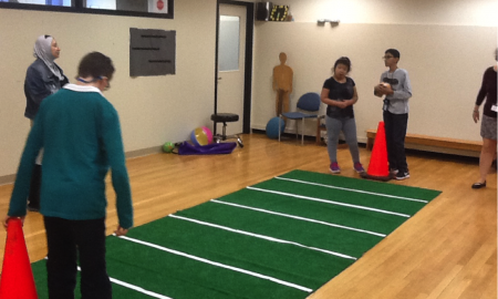 2 students standing on either end of a football carpet