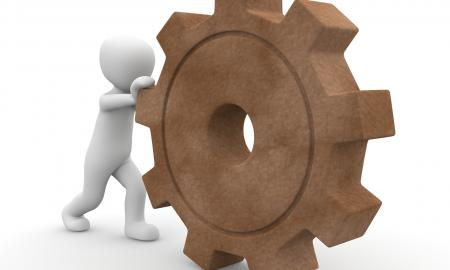 A character is pushing a cog wheel