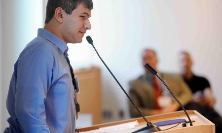 A young man giving a speech at a podium.