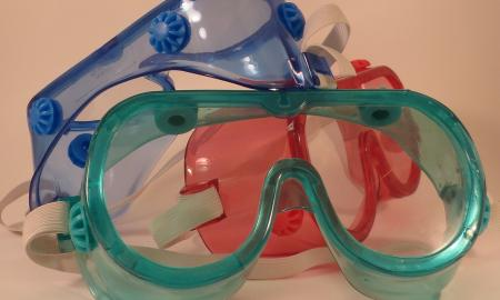 Three pairs of safety goggles in a pile.