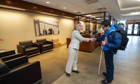 A teen who is blind shakes the hand of a woman in a bank.