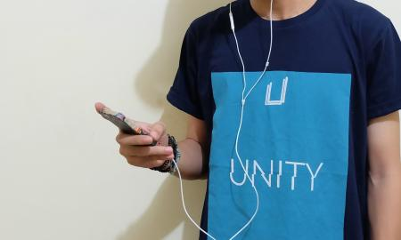 a boy wearing a blue shirt listening to his iPod