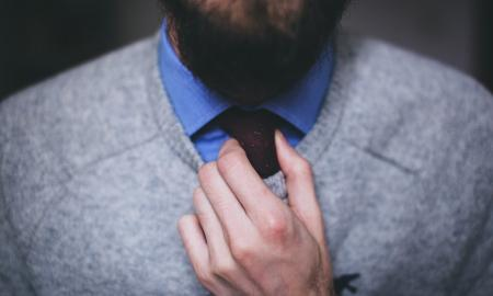 a man with a beard, wearing a blue shirt and grey sweater adjusting his tie