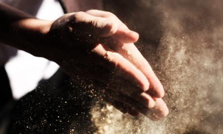 two hands together as if clapping, with dust floating around them