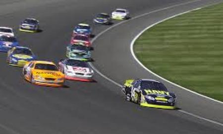 The image is of race cars turning on a racetrack.