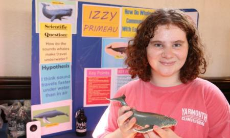 Girl showing model whale in her science fair project.