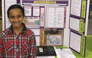 Hari standing next to Science Fair Project