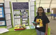 Hari standing by her Science Fair project