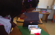 A girl with low vision looks at the light from a flashlight shining onto a black card