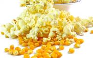 poppy and unpopped kernels of popping corn spilled on a table