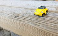 Image of a small yellow toy car on a wooden plank