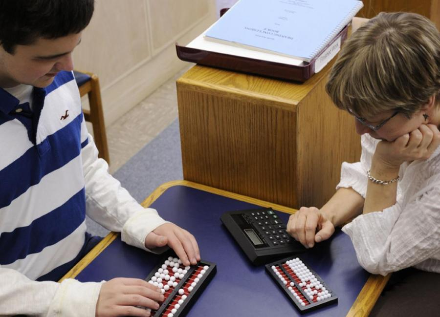 Student using abacus with teacher