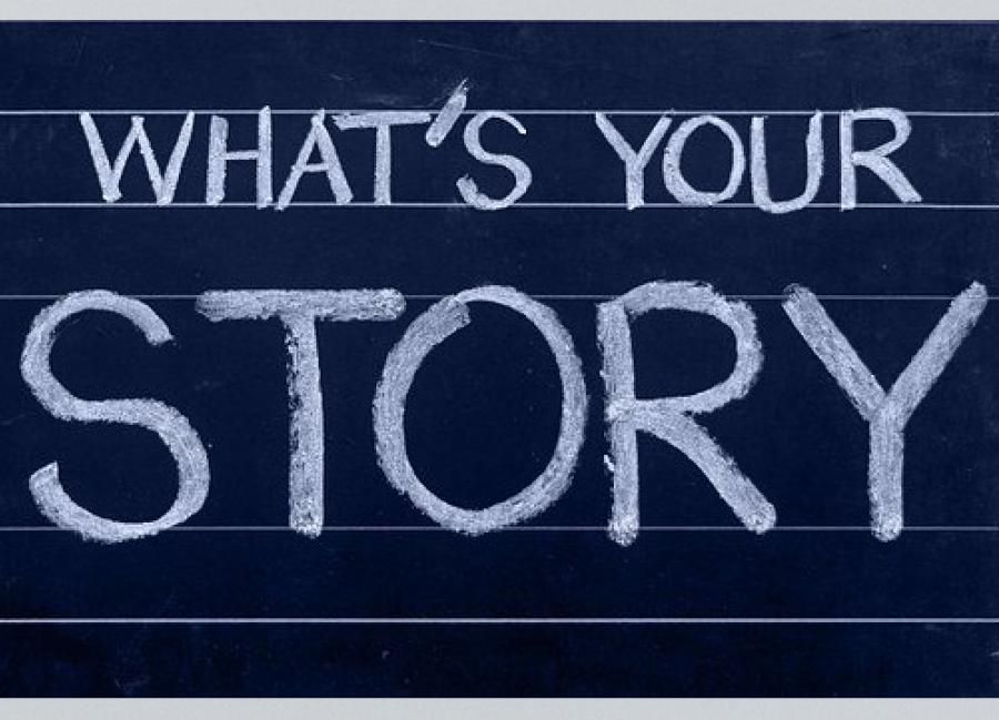 """""""What's Your Story"""" written in chalk on a chalk board."""