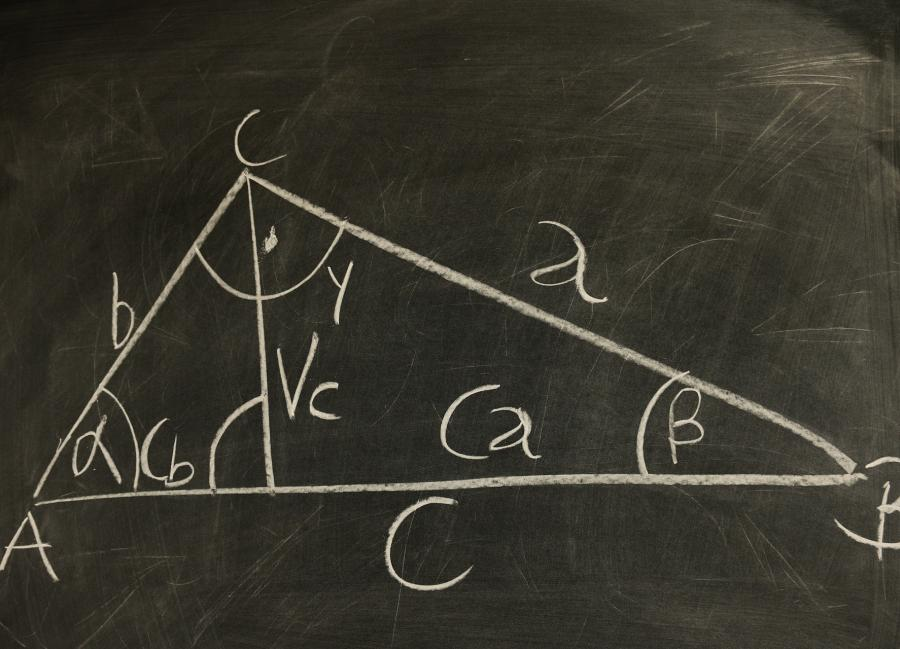 a triangle with labeled sides and measured angles on a chalkboard