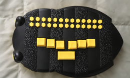 BrailleBuzz, a black & yellow bee shaped toy for braille readers with honeycomb shaped braille letter keys & Perkins keyboard.