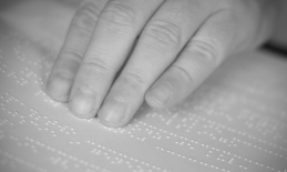 image of fingers reading a braille book