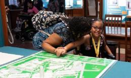 teacher guides a student through a large 3D map