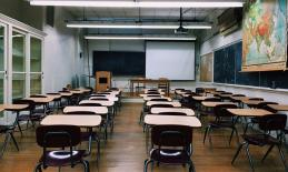photo from the back of an empty classroom, demonstrating how far away the whiteboard is, emphasizin the need for accommodations.
