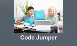 Boy and girl sitting at a table playing with Code Jumper pods and a tablet.