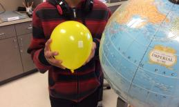 A student stands with the Moon (a balloon) facing the Earth.