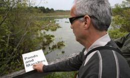 Jerry Berrier reads Ponds and Marshes sign