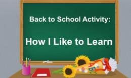 """Teacher's desk with  """"Back to school Activity: How I Like to Learn"""" written on the chalkboard."""