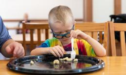 young boy with glasses uses hands and fork to spear a bite