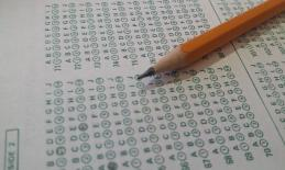 Pencil filling in a bubble answer sheet.