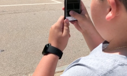 Student standing on a street corner using his iPhone to magnify and trace the curb across the street.