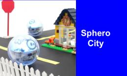 """Sphero ball rolling along street lined with lego house in the background & picket fence with text, """"Sphero City""""."""