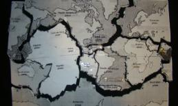Tectonic plates shown cut out and labeled in print and braille.