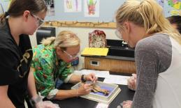 two female students dissecting a frog with a female teacher