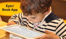 "Young boy holding and looking intently at an iPad with text, ""Epic! Book App"""