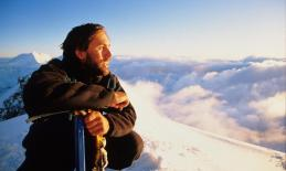 Erik Weihenmayer on the summit of Denali with clouds and snow covered mountain ranges in the background