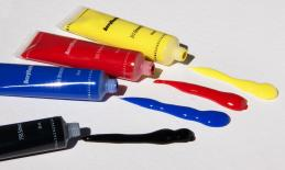 four tubes of puffy paint in black, red, blue, and yellow