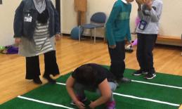 "student prepared to ""hike"" the ball on green carpet"