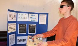 student standing in front of his science fair poster