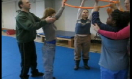 A small group of students lift a hula hoop above their heads.