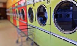 a row of different colored washing machines with a wire laundry cart in front of them