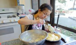 A teenage girl makes mashed potatoes.