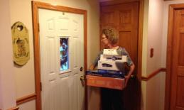 A woman carries multiple boxes to the front door.