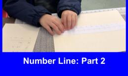 Logan's hands on a tactile number line with a braille math worksheet beside him.