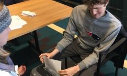 A young man sits on a chair and uses a paper shredder.