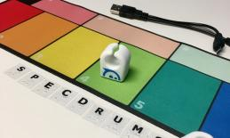 "SpecDrums color board, 2 finger rings, and print/braille letters spelling, ""SpecDrums""."
